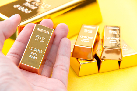 Hand hold gold bars Stock Photo