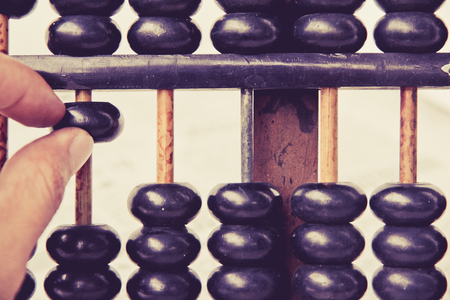 sums: close up image of hand accounting with old abacus. financial concept Stock Photo