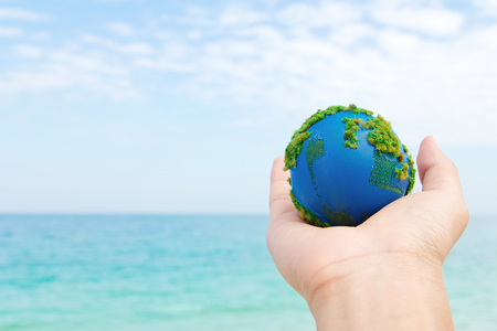 global environment: Earth in hand with nature background