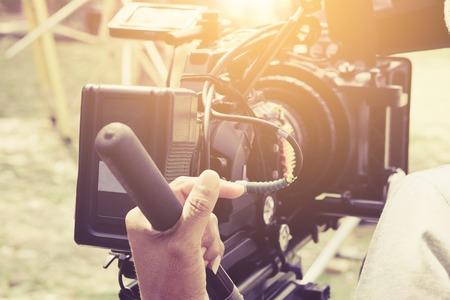撮影、手を調整するカメラ、フィルムの生産乗組員、シーンの背景の背後にある彼のビデオカメラを持つカメラマン。 写真素材