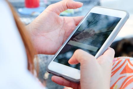 Teenage girl using white mobile phone