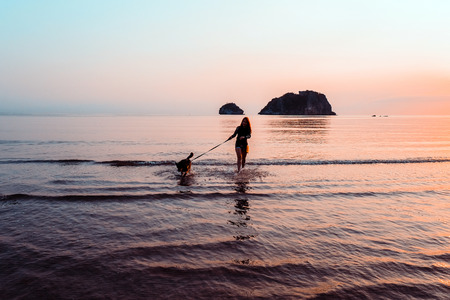 Woman and dog on beach at sunrise Stock Photo