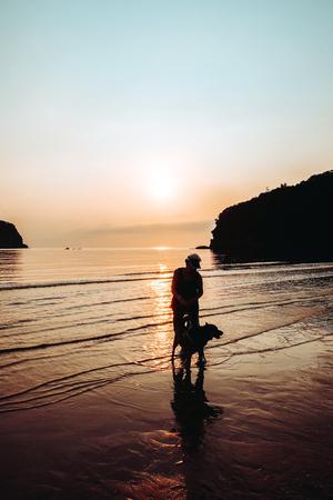 Senior Woman and dog on beach at sunrise