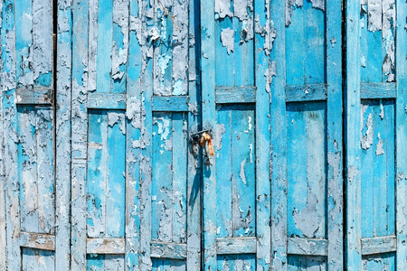 Detail of Old shabby blue wooden door background