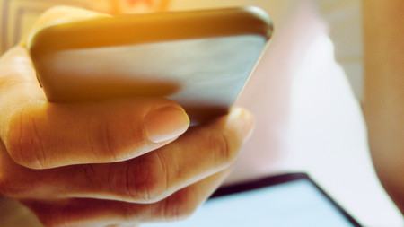 Closeup Image of mans hand holding a smartphone Stock Photo