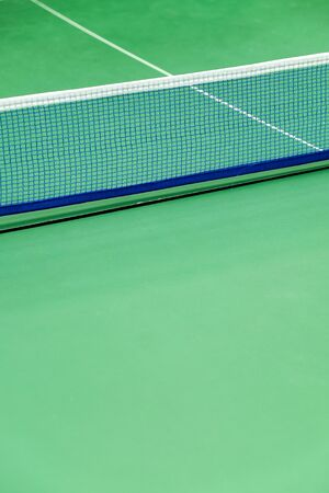 Net of tennis court on green wall background