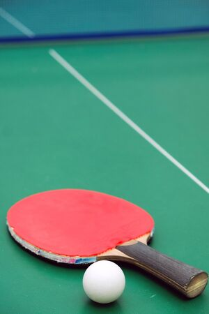 Table tennis racket with a ball on green background.