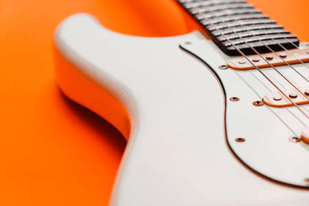 Detail of White Electric Guitar on a orange background. 免版税图像