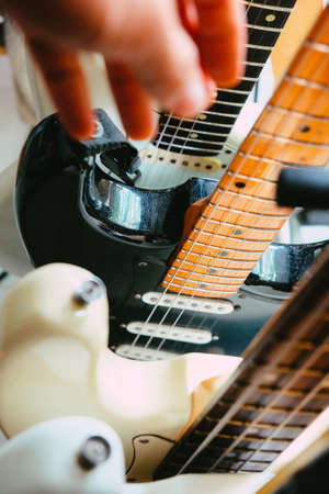 close up Image of Hand picking up guitar