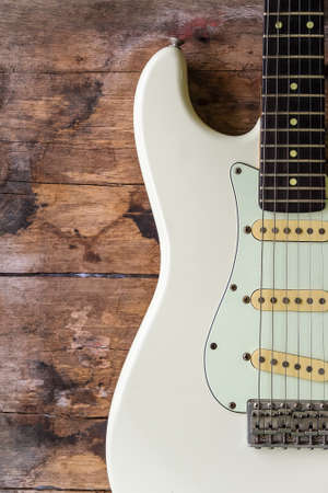 Detail of White Electric Guitar on a wood background.