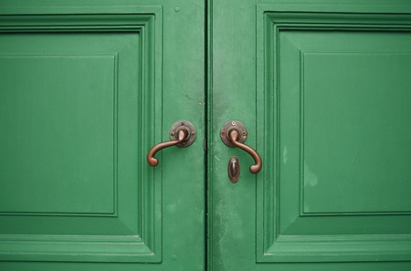 Door handles with an old double wood door green photo
