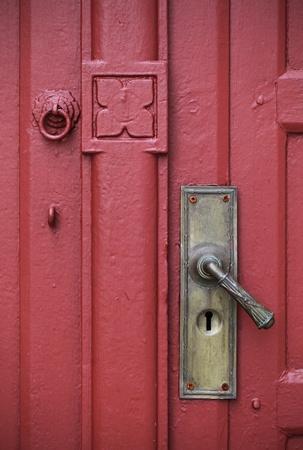 Door handle with an old double wood door painted red color photo