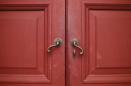 Door handles with an old double wood door red Stock Photo - 12555692