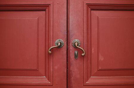 Door handles with an old double wood door red Stock Photo - 12555692