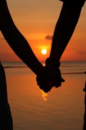 siluetas de enamorados: Siluetas parejas cogidos de la mano. Foto de archivo
