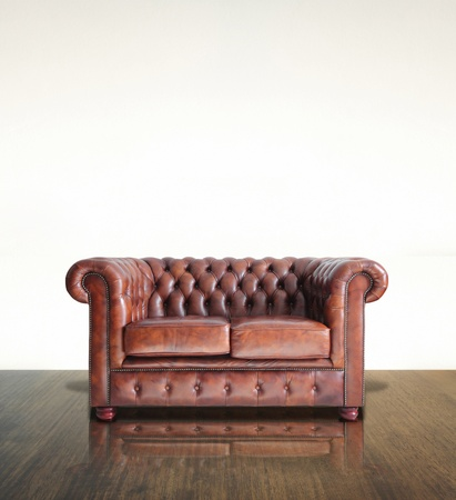 brown leather sofa: Classico Divano in pelle marrone e sfondo di legno vecchio