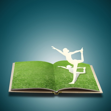 Paper cut of girl doing yoga on old book grass photo