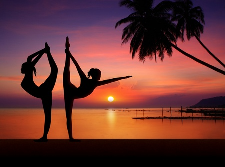 Silhouette of Yoga girls in sunset photo