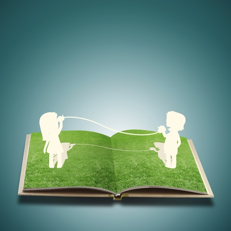 Paper cut of child on grass book photo