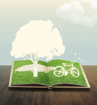 conceptual symbol: Paper cut of bicycle on grass book