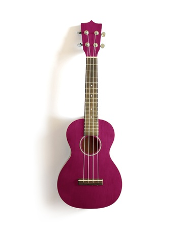 acoustic ukulele: pink old ukulele on white isolated