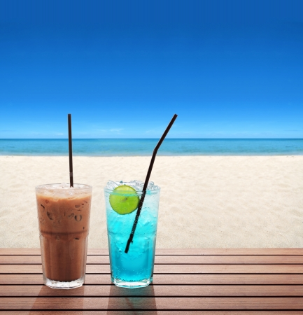 sweet table: ice coffee with blue soda with lime on the summer beach Stock Photo
