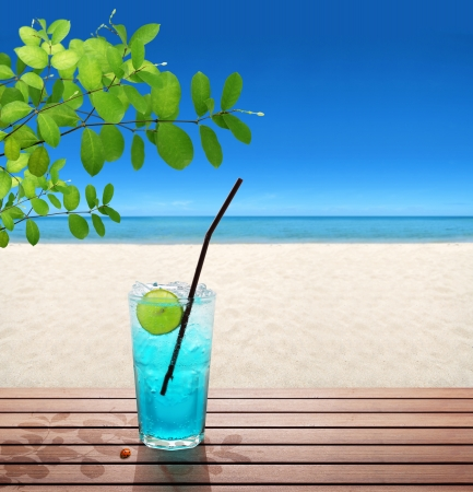 blue soda with lime under tree on the beach photo
