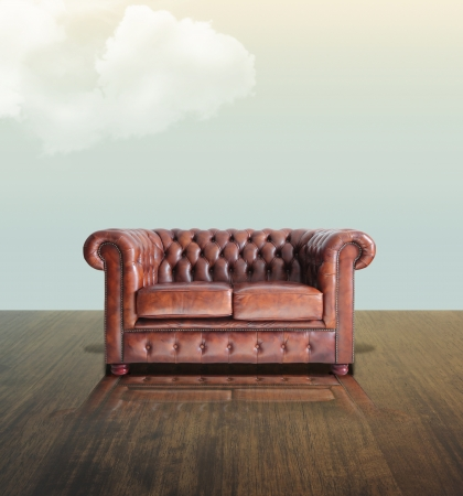 Classic Brown leather sofa on wood under the sky background.  photo