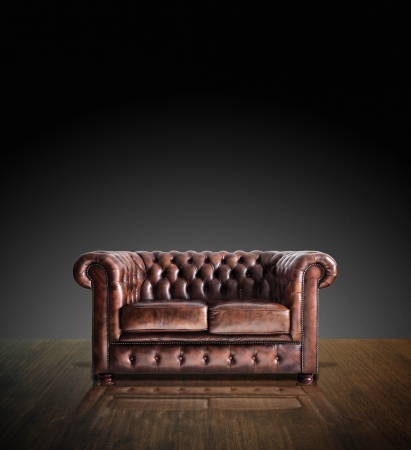 couch: Classic Brown leather sofa on wood in darkroom background