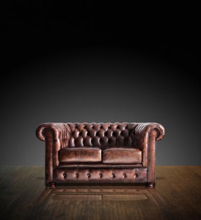 brown leather sofa: Classico divano in pelle marrone su legno in camera oscura sfondo