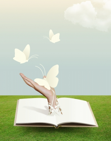 butterfly hand: open book on grass with butterfly in hand  Stock Photo