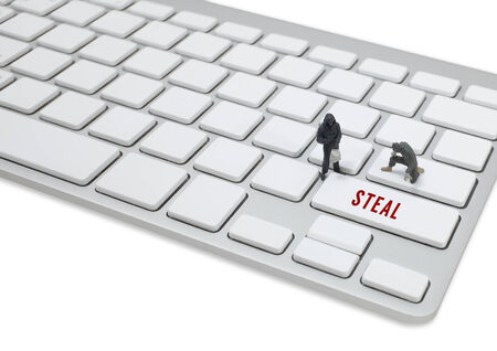 company secrets: thief man miniature figure concept steal data on keyboard Stock Photo