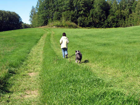 black moor: A bearded collie chasing a woman acrss the field.