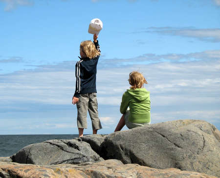 Waving boy and sitting girl by the ocean photo
