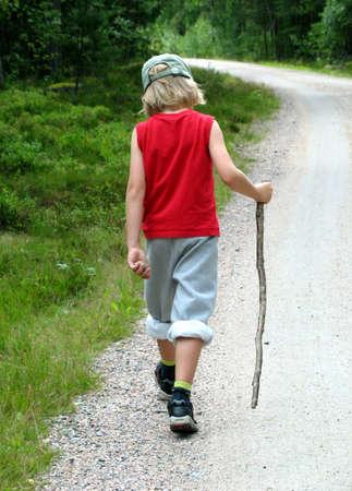 Boy walking during hike, with a stick Foto de archivo