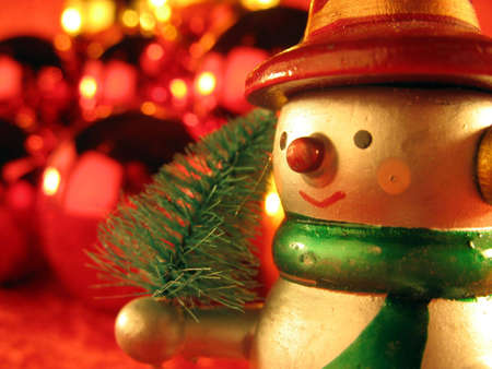 Snow man with a little christmas tree photo