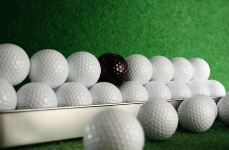 Golfballs with a bad friend amongst them photo