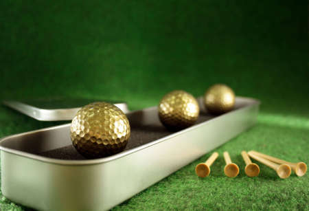 Golden golfballs in gift set for luxury play Stock Photo