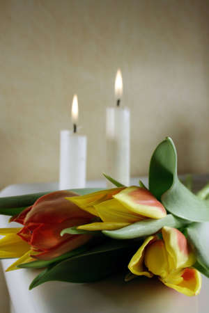 Tulips in red and yellow with candles behind, for wedding or funeral Foto de archivo