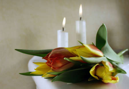 Tulips in red and yellow with candles behind, for wedding or funeral Stock Photo