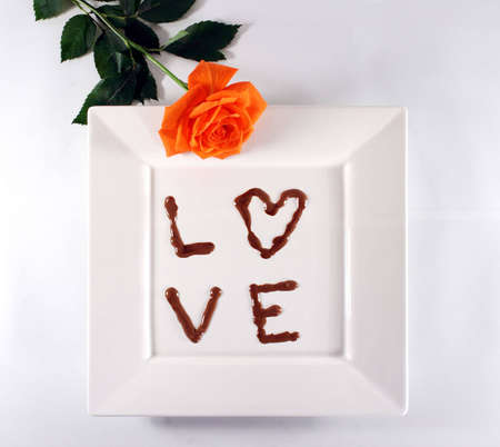 Love in chocolate on white plate with rose. photo