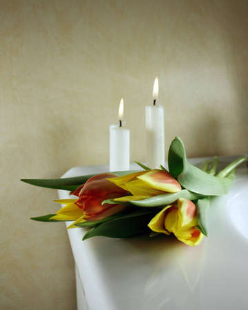Beautiful tulips in red and yellow with candles behind, for wedding or funeral Foto de archivo