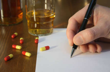suicidal: Suicidal person writing a message next to whisky and pills