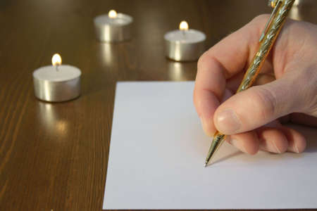 noting: Hand wiriting with golden pen with candles Stock Photo
