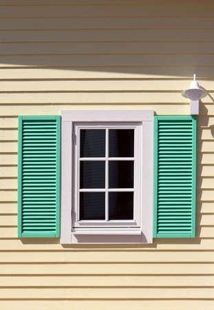 Window with green shutters on yellow wall Foto de archivo