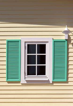 Window with green shutters on yellow wall Stock Photo