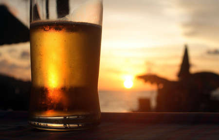Beer in the sunset on the beach Stock Photo