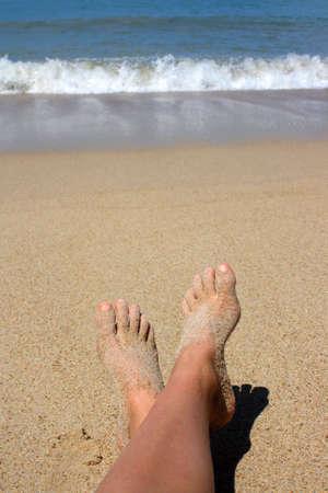 Feet on the beach by the ocean photo