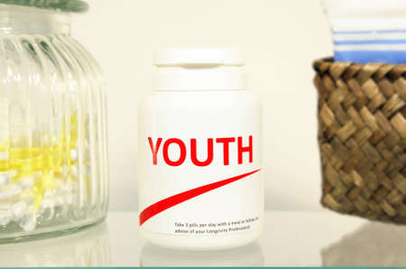 longevity drugs: Youth pills in a bottle on bathroom shelf, fake brand Stock Photo