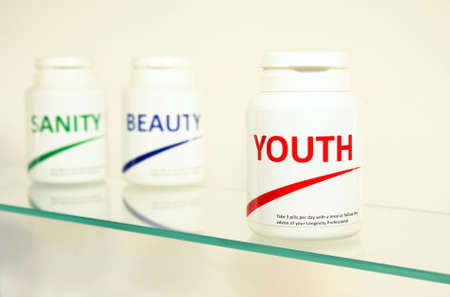 longevity drugs: Sanity, Beauty and Youth pills in a bottle on bathroom shelf with focus on Youth, fake brands Stock Photo